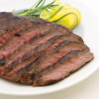 Grilled medium-cooked flank steak. Garnish of rosemary sprig