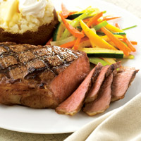 Thinly sliced, medium rare New York steak, grilled with criss cross pattern, on plate with baked potato topped with butter and sour cream and julienne vegetables
