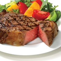 Thick, grilled steak with criss cross pattern sliced once to show rare meat, on plate with salad of spring mix and quartered slices of yellow and red tomatoes