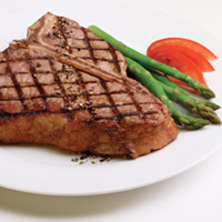 Grilled T-bone with criss cross pattern. Asparagus tucked to the side of plate and garnish of bright red sliced tomato