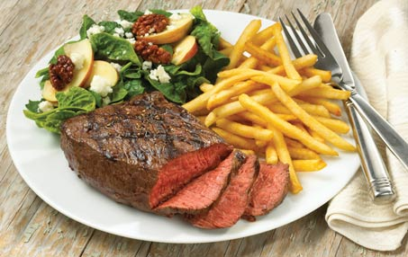 Plate of sliced grilled steak, french fries and spinach salad with candied walnuts, apple slices and goat cheese crumbles