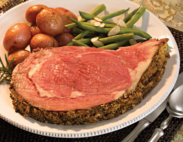 White plate filled with slice of rare prime rib. Roasted red potatoes and green beans almandine at top of plate