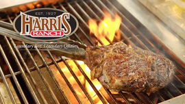 Flaming grill with steak, tongs and Harris Ranch logo