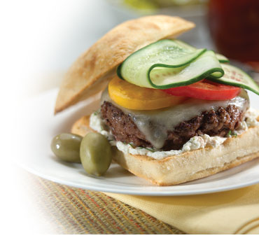 Burger on toasted sourdough bun and bed of creamy cheese, topped with melted jack, red and yellow bell peppers and cucumber slices. Two green olives on plate with burger
