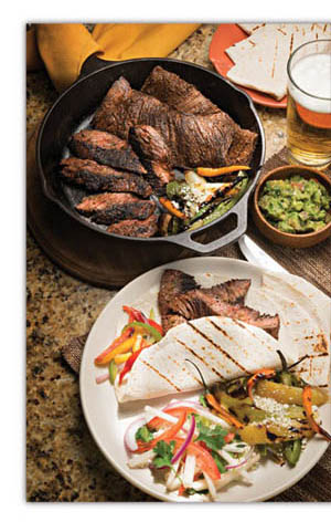 Black, cast iron skillet with cooked beef, small wooden container of guacamole, plate of grilled steak fajitas with sliced bell peppers and onions