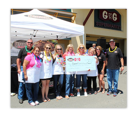 group of 8 men and women in aprons under a Harris Ranch tent canopy in parking lot in front of G G Market holding a large check signifying donation. Amount of check written too small to discern