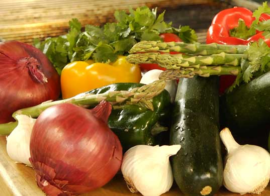 Close up of wood table top with fresh, raw veggies: red and white onions, asparagus, red and yellow bell peppers, cucumber