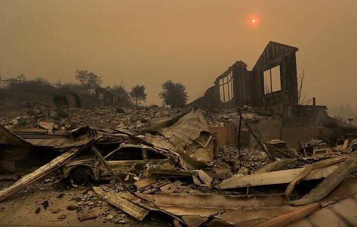 Devastation from scene of recent fire. Burned out car, collapsed structure with only one partial wall remaining, yellow sun high in smokey sky, shrouded with orange ring
