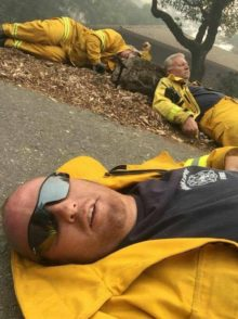 3 male firefighters in yellow protective clothing, laying on ground, exhausted. Smokey air.