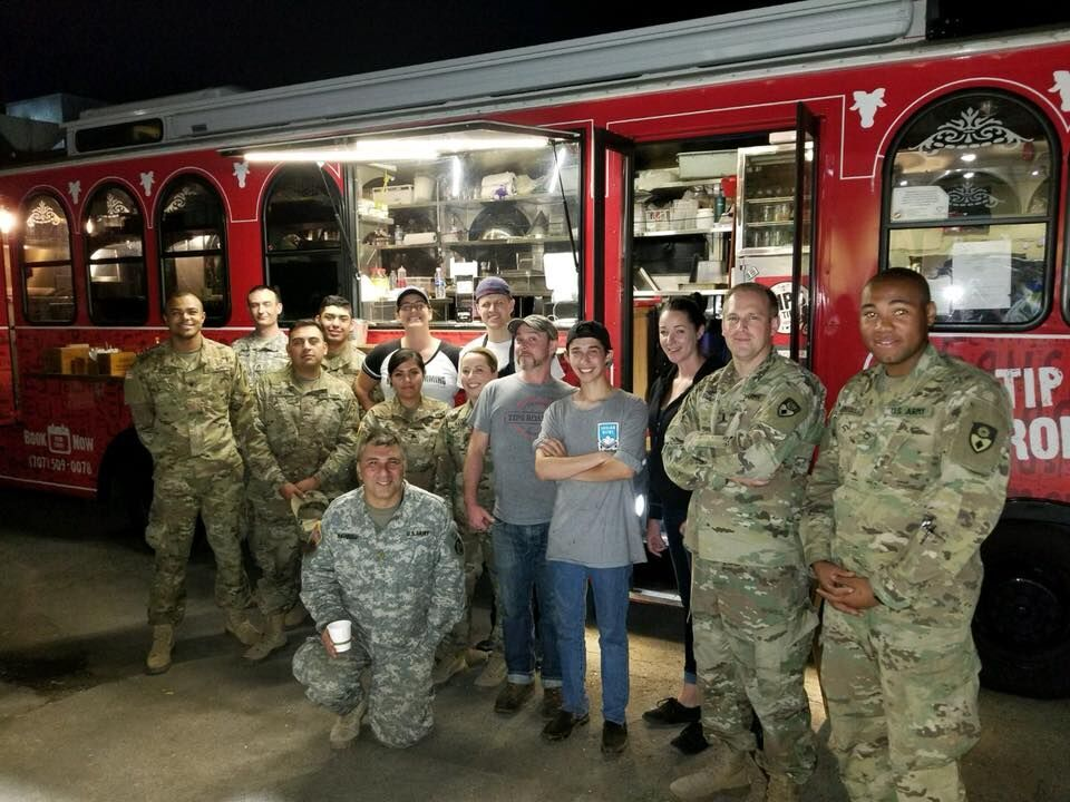 9 military men and women dressed in camo standing in front of red catering trolley with 5 men and women who staff the trolley
