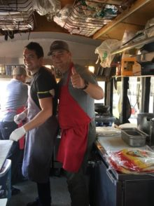 Two smiling men in BBQ aprons, one with thumbs up, inside catering trolley