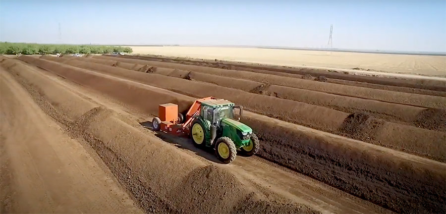 Tractor driving between rows of piled compost taken from Harris Feeding Company feedlot